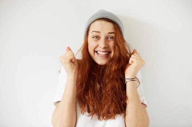 Kopfschuss der jungen glücklichen frau, die graue mütze und t-shirt mit freudigem gewinnendem lächeln trägt