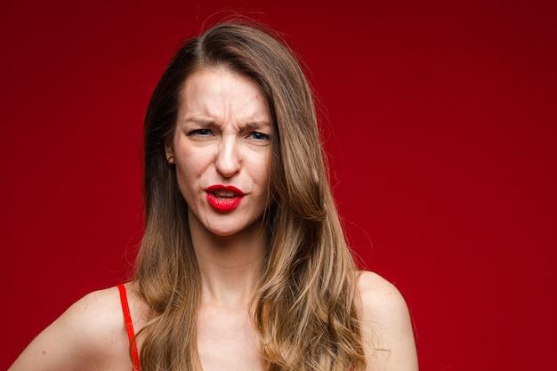 Kopfschuss der jungen unzufriedenen ernsthaften frau, die auf roter wand mit kopierraum für werbung die stirn runzelt