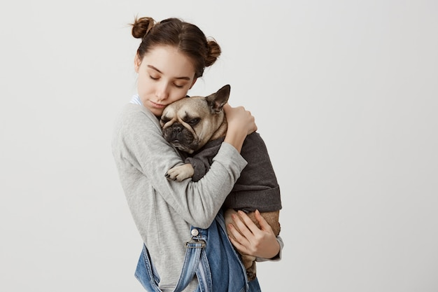 Kopfschuss der kaukasischen frau mit geschlossenen augen, die ihr reizendes haustier wie kind halten, das zusammen entspannt. zarte gefühle des niedlichen mädchens, das ihren kleinen hund kuschelt, der in pullover gekleidet wird. pflege, liebeskonzept