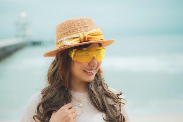 Kopfschuss der schönen asiatischen frau, die gelbe brillen trägt, die am meeresstrand stehen