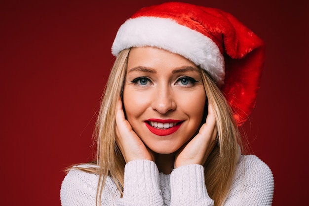 Kopfschuss der schönen blonden kaukasischen frau mit den roten lippen, die die weihnachtsmütze tragen, die hände an den wangen hält, lächelnd.