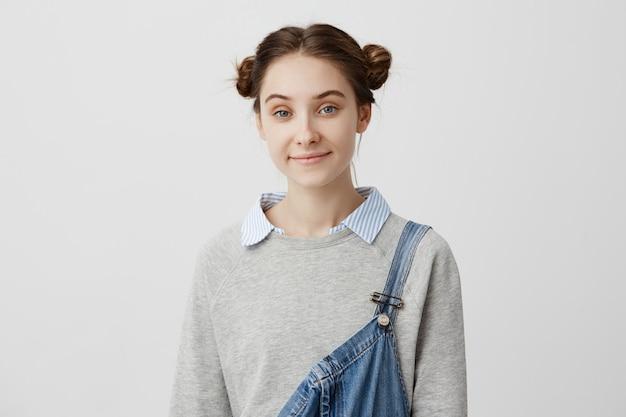 Kopfschuss der schönen frau 20s mit europäischem aussehen, das über weißer wand steht, die aufrichtig lächelt. weibliche schauspielerin in jeansoveralls beim casting für einen neuen film. glückskonzept