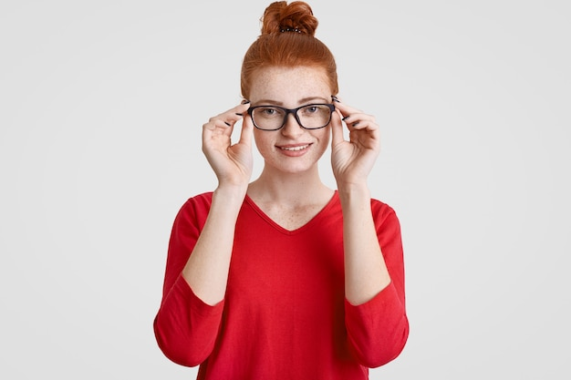Kopfschuss der schönen sommersprossigen jungen europäischen frau in brille, hat sanftes lächeln, gekleidet in roten pullover
