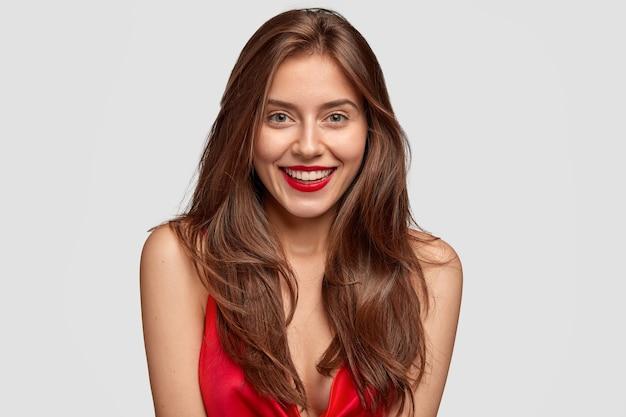 Kopfschuss der schönen sorglos lächelnden herrlichen dame mit dunklem haar, roten lippen