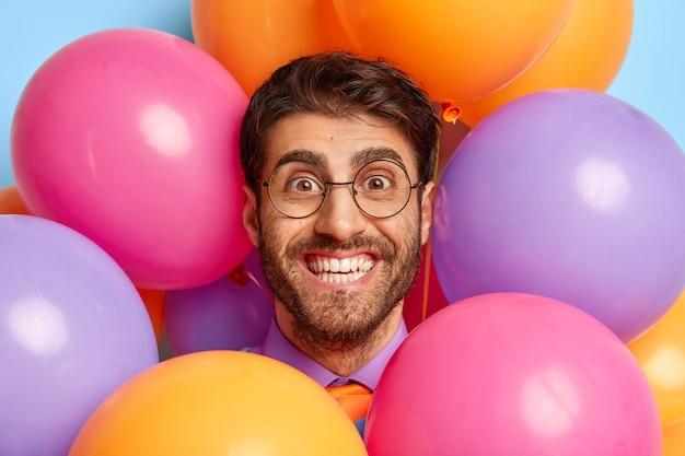 Kopfschuss des gutaussehenden kerls, umgeben von partyballons, die aufwerfen
