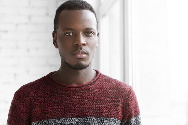 Kopfschuss des hübschen jungen unrasierten afrikanischen mannes, der lässigen gemütlichen pullover trägt