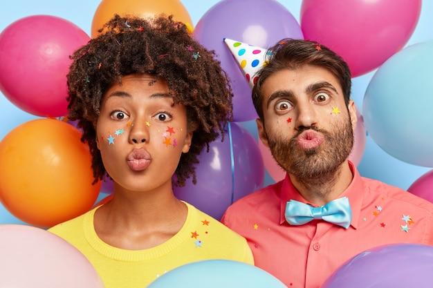 Kopfschuss des lustigen jungen paares, das durch bunte luftballons des geburtstages posiert