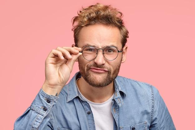 Kopfschuss des mysteriösen europäischen jungen freundes schmollt lippen in die kamera, trägt runde transparente brille, hat faszinierenden blick in die kamera