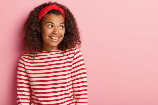 Kopfschuss des schönen teenager-mädchens mit dem lockigen haar, das im gestreiften roten pullover aufwirft