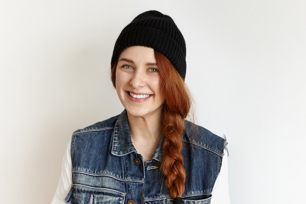 Kopfschuss des schönen weiblichen modells mit blauen augen und niedlichem fröhlichem lächeln, das an der weißen wand aufwirft