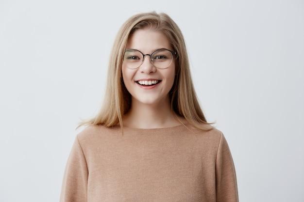 Kopfschuss einer angenehm aussehenden jungen kaukasischen frau, die eine brille mit einem breiten lächeln trägt und zeigt, dass ihre geraden weißen zähne wegen positiver nachrichten glücklich sind. blondes mädchen mit angenehmem lächeln