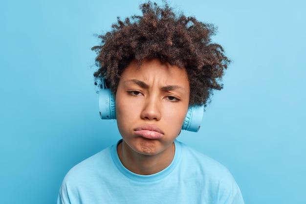 Kopfschuss einer frustrierten afro-amerikanerin mit lockigen haartaschenlippen macht eine unglückliche grimasse, hört audiospur in kopfhörern, die nach dem spaziergang über blaue wand müde sind schlechte emotionen