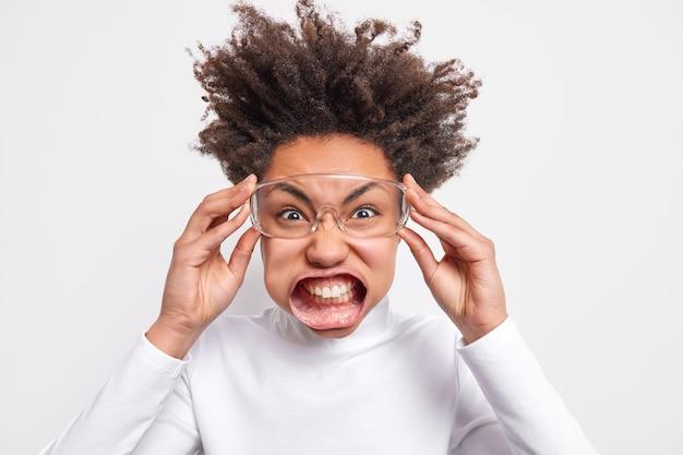 Kopfschuss einer gereizten, lockigen frau, die die zähne zusammenbeißt, grinst das gesicht aus wut aus, trägt eine transparente brille, weißer rollkragenpullover posiert drinnen, ist super verrückt und sehr wütend auf jemanden.
