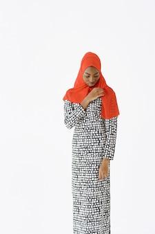 Kopfschuss einer schönen, zufriedenen, religiösen muslimischen frau mit sanftem lächeln, dunkler gesunder haut, trägt schal auf dem kopf. getrennt über weißem hintergrund.