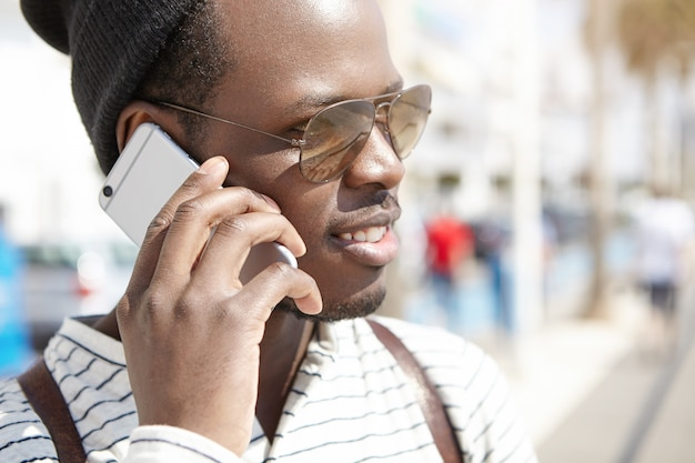 Kopfschuss einer schwarzen person in schattierungen, die am sonnigen frühlingstag ein telefongespräch führt und einen schönen spaziergang auf den straßen des ferienortes genießt. menschen in den ferien. jugend und reisen. mensch und technik