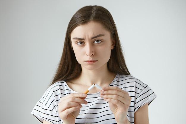Kopfschuss einer selbstbestimmten ernsthaften jungen dunkelhaarigen europäischen frau in freizeitkleidung, die zwei hälften zerbrochener zigarette in den händen hält, mit dem rauchen aufhört und schlechte destruktive angewohnheiten bricht