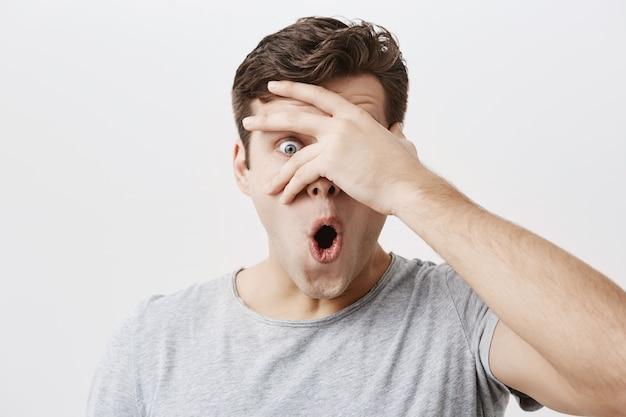 Kopfschuss eines doof überraschten jungen europäischen studenten mit käferaugen, der ein lässiges graues t-shirt trägt, das mit schockiertem blick starrt, erstaunen und schock ausdrückt und sein gesicht hinter seiner handfläche versteckt.