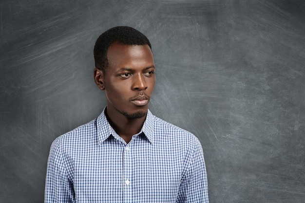Kopfschuss eines ernsthaften nachdenklichen jungen afrikanischen mathematiklehrers im freizeithemd, der mit nachdenklichem ausdruck beiseite schaut, an der tafel im klassenzimmer steht und auf seine schüler für die nächste lektion wartet
