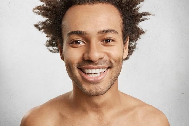 Kopfschuss eines nackten mannes mit ansprechendem aussehen, lächelt fröhlich, zeigt weiße, gleichmäßige zähne