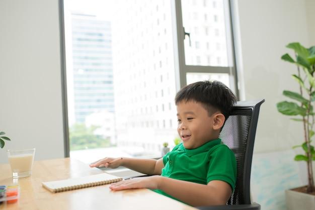 Kopfschuss portrait eines glücklichen asiatischen netten kindes, das zu hause hausaufgaben mit lächelngesicht macht.