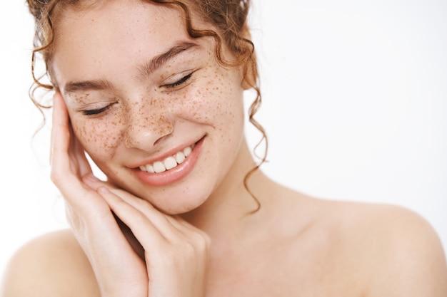 Kopfschuss zart glücklich lächelnd nackte rothaarige frau sommersprossen berühren perfekt saubere reine haut enge augen erleichtert entspannt lachen freudig die ergebnisse der hautbehandlung genießen, auf den weißen hintergrund des körpers achten