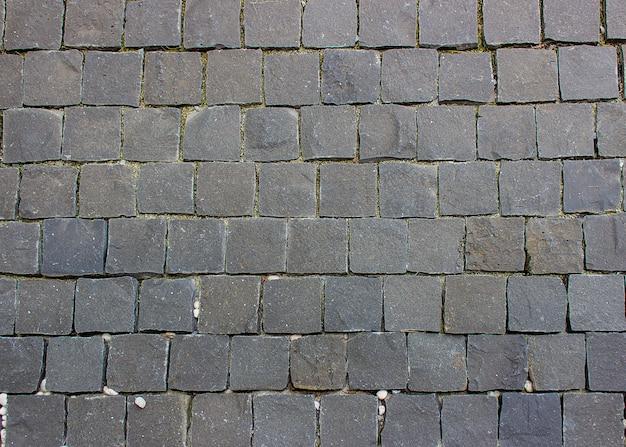 Kopfsteinpflaster, altes mauerwerk auf dem bodenhintergrund