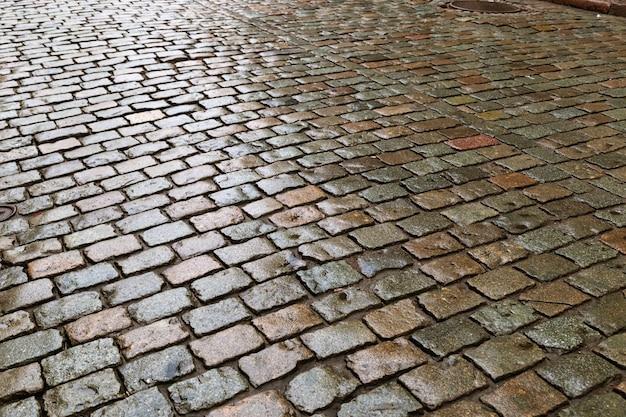 Kopfsteinpflaster. große quadratische felsbrocken steine auf der straße. straßenbelag.