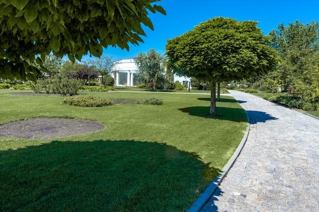 Kopfsteinpflasterweg, der durch grünen rasen zum weißen landhaus führt