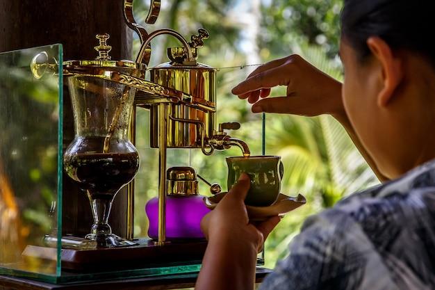 Kopi luwak macht legendären kaffee in einem vintage-siphon. bali, indonesien