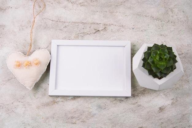 Kopienraum des weißen rahmens der draufsicht, saftiger topf und herz auf marmorhintergrund