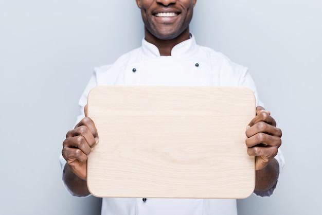 Kopieren sie platz auf seinem schneidebrett. nahaufnahme eines selbstbewussten jungen afrikanischen kochs in weißer uniform