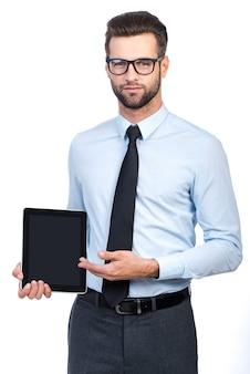 Kopieren sie platz auf seinem tablet. selbstbewusster junger gutaussehender mann in hemd und krawatte, der ein digitales tablet hält und mit einem lächeln darauf zeigt, während er vor weißem hintergrund steht