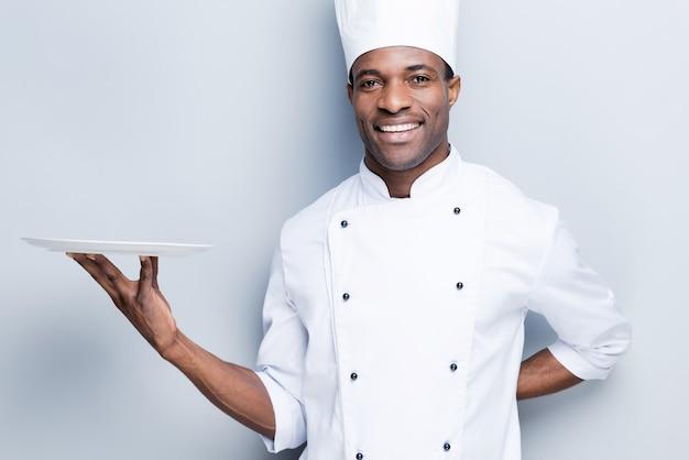 Kopieren sie platz auf seinem teller. selbstbewusster junger afrikanischer koch in weißer uniform mit leerem teller