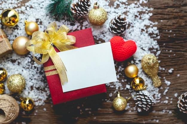 Kopieren sie platz grußkarte auf weihnachtsgeschenkbox mit weihnachtszusammensetzung auf holztisch.