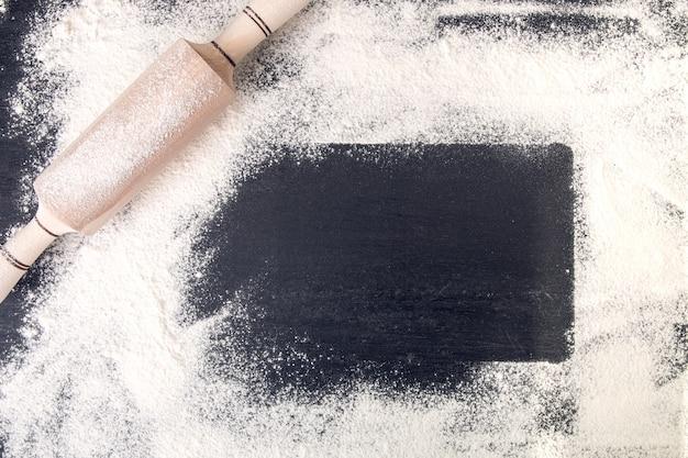 Kopieren sie platz um nudelholz und mehl auf schwarzem hintergrund.