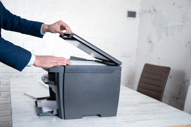 Kopiergerät des jungen mannes, der im büro arbeitet