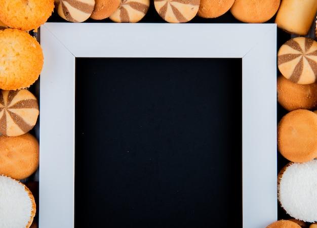 Kopierraum der draufsicht mischen kekse mit marshmallows und einem weißen rahmen mit einem schwarzen hintergrund