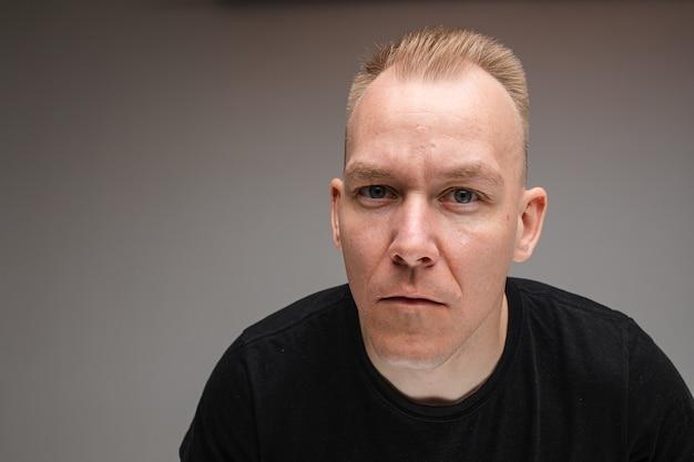Kopierraumfoto des ernsten kaukasischen mannes im schwarzen hemd, das seine stirn runzelt