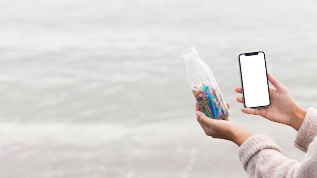 Kopierraumfrau, die foto der flasche mit plastik macht