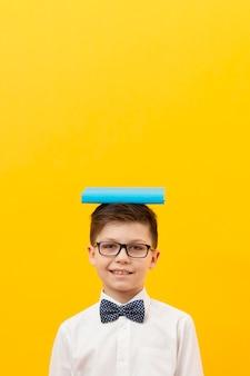 Kopierraumkind mit buch auf dem kopf