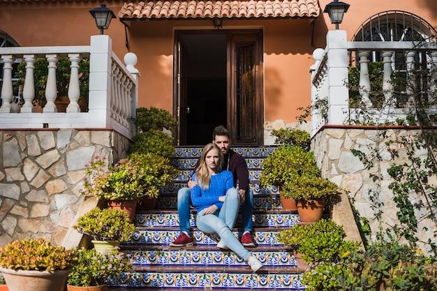 Koppel sitzt draußen auf der treppe