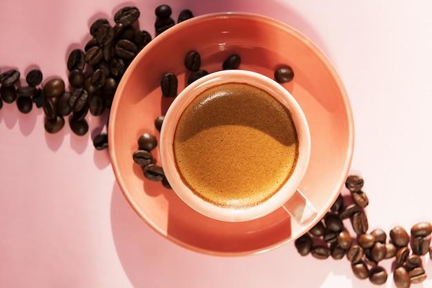 Korallenfarbene tasse mit kaffeebohnen mit schatten auf pastellrosenhintergrund. flach liegen. draufsicht. kaffeekonzept. sommerstillleben