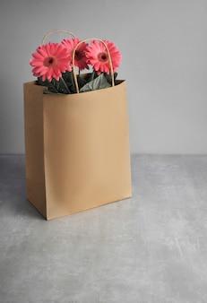 Korallengerbera-gänseblümchenblumen und bastelpapier-einkaufstaschen auf grünem papierhintergrund, text
