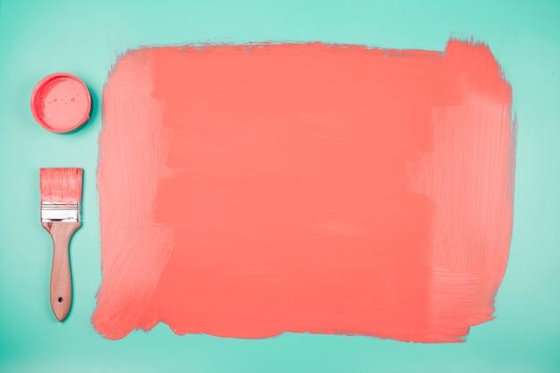 Korallenrote farbe kann und malerpinsel mit gemaltem aquamarinem hintergrund
