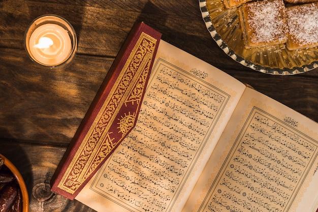 Koran in der nähe von kerze und dessert