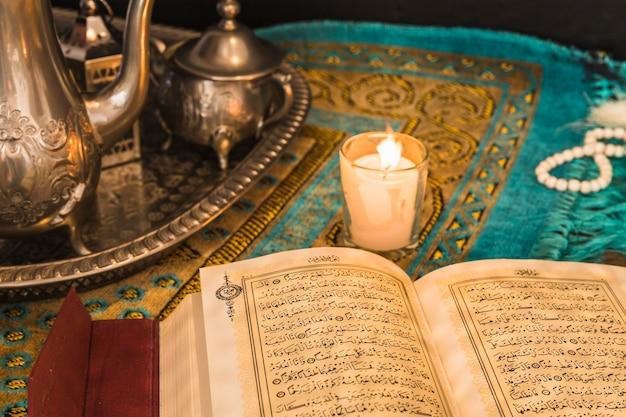 Koran in der nähe von kerze und tablett mit geschirr