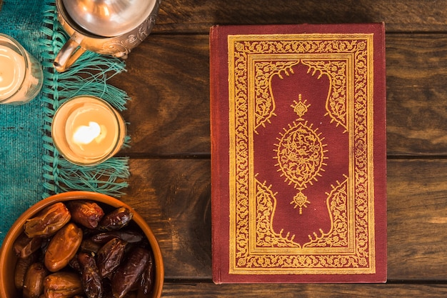 Koran in der nähe von süßen datteln und kerzen