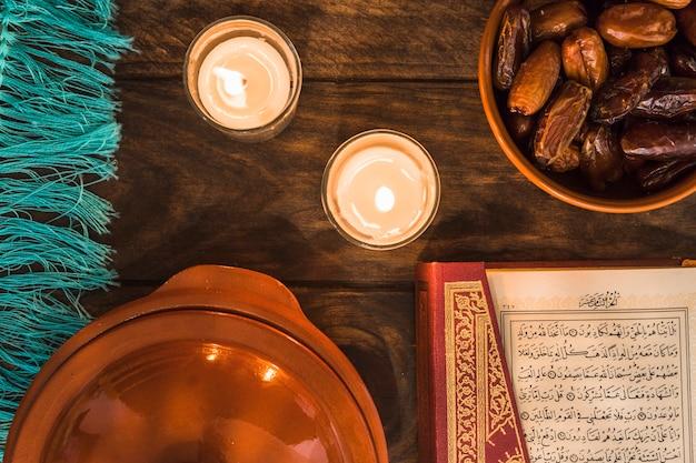 Koran und datteln in der nähe von brennenden kerzen
