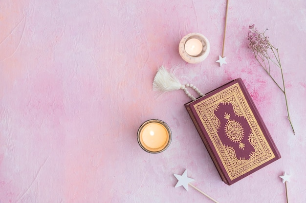 Koran und kerzen auf rosa