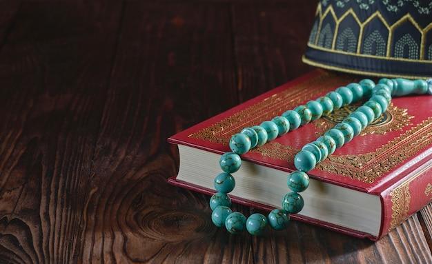 Koran und rosenkranz auf holztisch